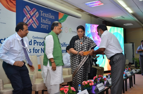 Smt. Smriti Zubin Irani Hon'ble Minister of Textiles and Shri Radha Mohan Singh, Hon'ble Minister of Agriculture and Farmers' Welfare being felicitated by Shri A Madhu Kumar Reddy, Joint Secretary (Jute), Ministry of Textiles on their arrival at the Dias for an International Seminar during Textile India 2017 at Gandhinagar, Gujarat